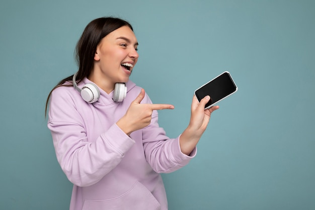 Mooie positieve lachende jonge donkerbruine vrouw, gekleed in paarse hoodie geïsoleerd op blauw