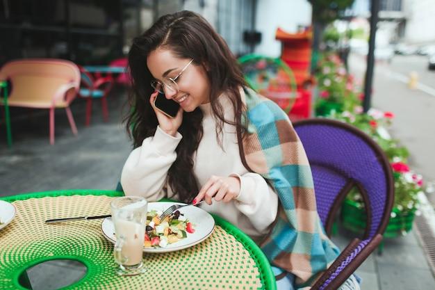 Mooie positieve vrouw praten over de telefoon tijdens de lunch