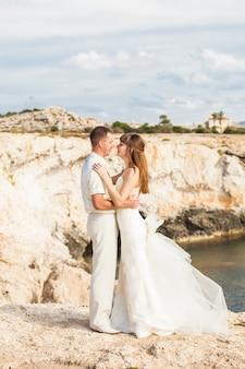 Mooie prachtige bruid en stijlvolle bruidegom op rotsen.