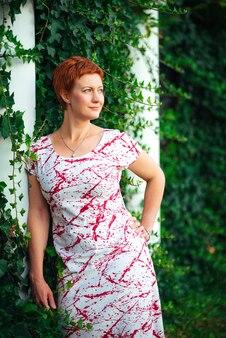 Mooie, prachtige en sexy roodharige vrouw poseren in de buurt van de muur van groen gebladerte en bladeren in de tuin, glamour en mode buiten zomer fotoshoot op aard