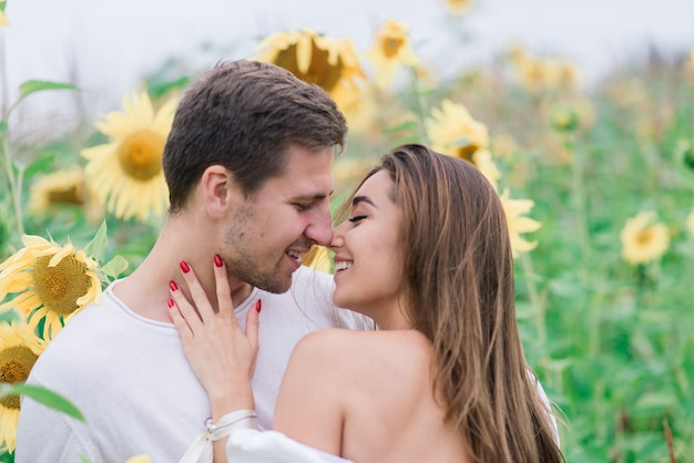 Mooie prachtige vrouw en stijlvolle knappe mannelijke, rustieke paar in een zonnebloem veld kussen, inschrijving