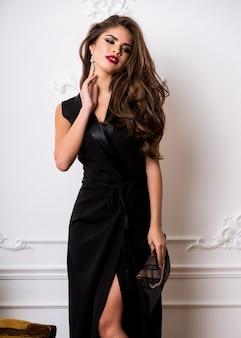 Mooie prachtige vrouw met rode volle lippen, smokey eyes make-up, perfecte golvende haren schijnt in elegante casual zwarte jurk poseren