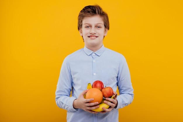 Mooie preteen jongen met fruit in de hand, in het blauwe shirt, geïsoleerd op gele muur