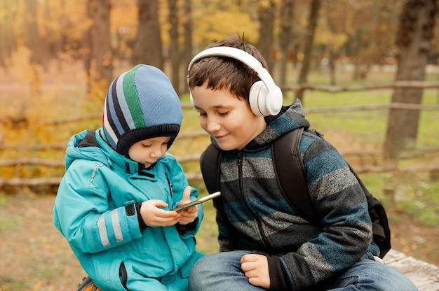 Mooie preteen jongen met zijn jongere broer die op het scherm kijkt