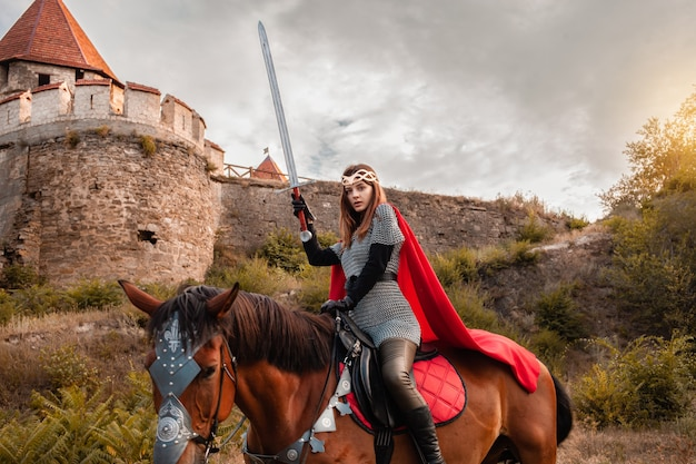 Mooie prinses met rode cape en met een zwaard op een paard tegen de achtergrond van een toren en