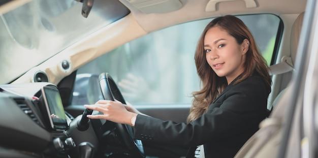 Mooie professionele aziatische onderneemster die terwijl het drijven van de auto glimlacht