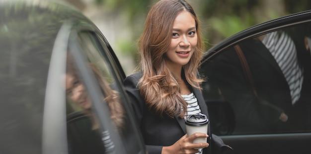 Mooie professionele onderneemster die van de moderne auto weggaat terwijl het houden van een koffiekop