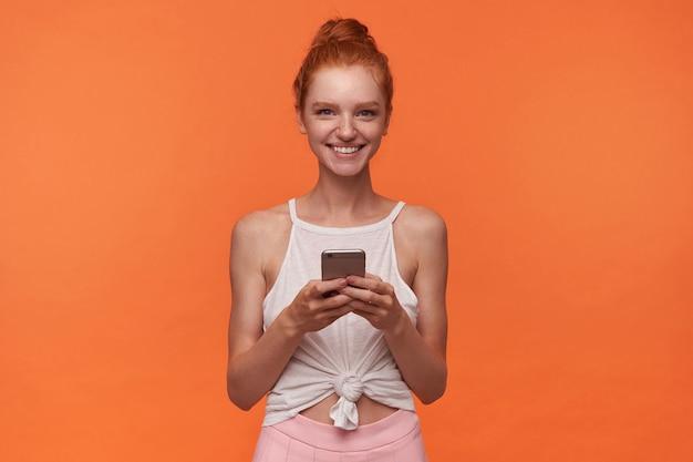 Mooie readhead vrouw met haar in knoop tonen haar aangename emoties, die zich voordeed op oranje achtergrond in witte top en roze rok, oprecht glimlachend naar camera met mobiele telefoon in handen