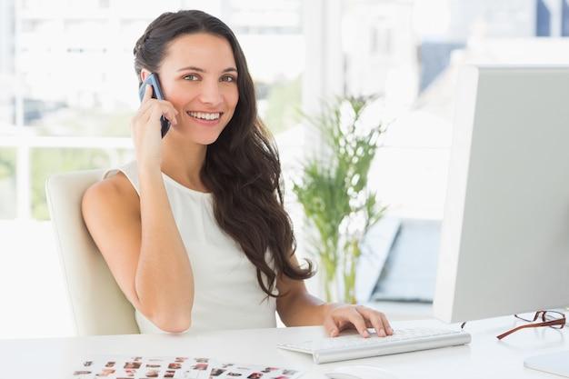Mooie redacteur die op telefoon bij haar bureau spreekt dat bij camera glimlacht