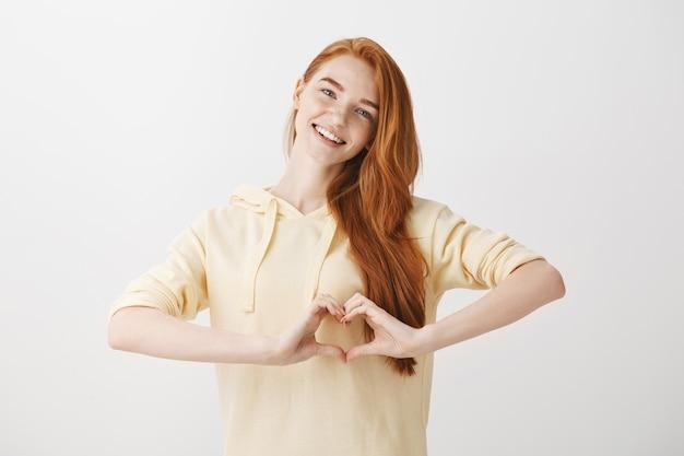 Mooie redead vrouw hart gebaar tonen en glimlachen