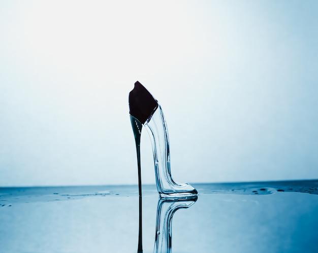 Mooie reflectie een glazen schoen op een blauwe abstracte achtergrond