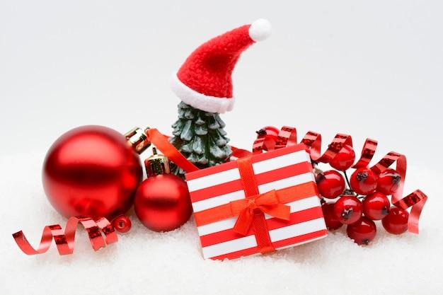 Mooie regeling van verpakte geschenkdoos met rode kerstballen en decor op witte sneeuw.