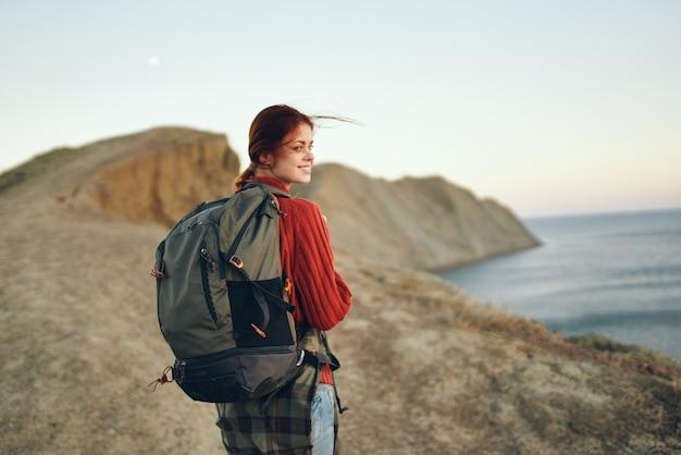 Mooie reiziger aan zee in de bergen en zonsondergang op de achtergrond bijgesneden weergave