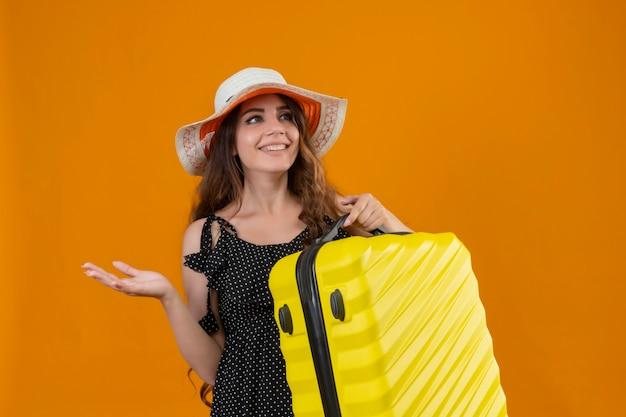 Mooie reiziger meisje in jurk in polka dot in zomer hoed bedrijf koffer opzij kijken met blij gezicht glimlachend vrolijk presenteren met arm van hand staande op gele achtergrond