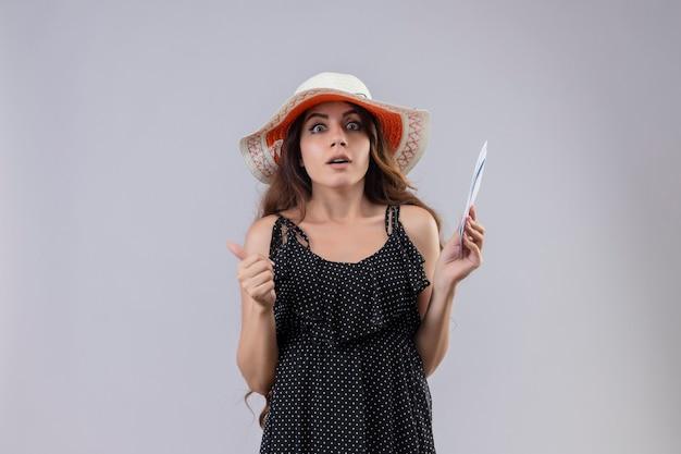 Mooie reiziger meisje in jurk in polka dot in zomer hoed met vliegtickets op zoek geschokt en bang staande op witte achtergrond