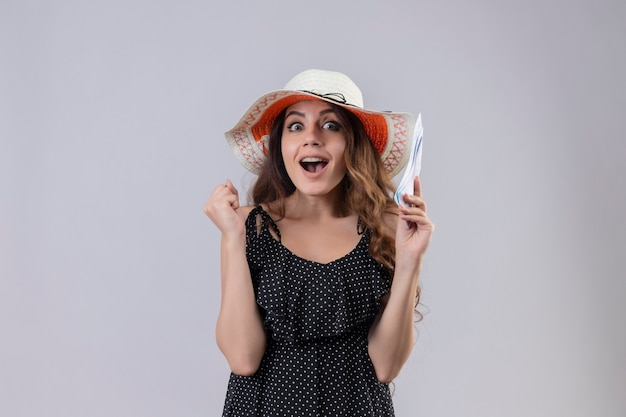 Mooie reiziger meisje in jurk in polka dot in zomer hoed vliegticket kijken op zoek verlaten en gelukkig verhogen vuist verheugend haar succes en overwinning staande op witte achtergrond