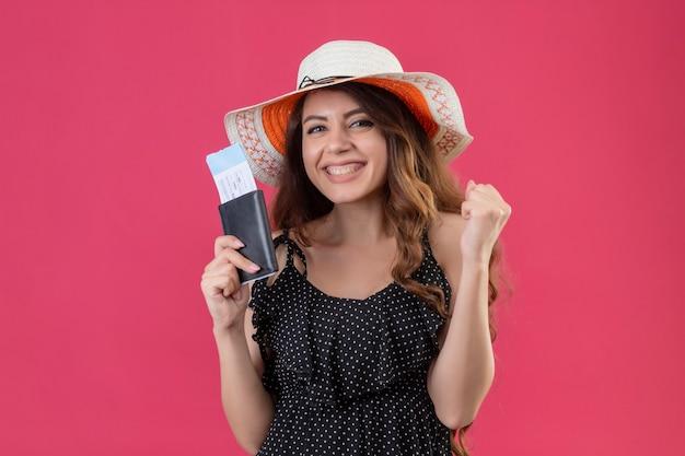 Mooie reiziger meisje in jurk in polka dot in zomer hoed vliegtickets koffer op zoek verlaten en gelukkig verhogen vuist verheugend haar succes en overwinning staande over roze achtergrond