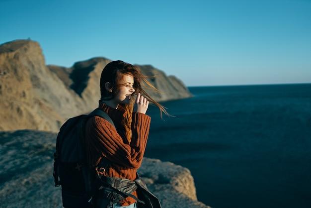 Mooie reiziger met een rugzak in de natuur vlakbij de zee