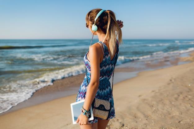 Mooie reiziger vrouw luisteren naar muziek op het strand