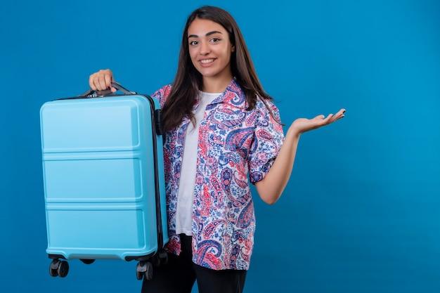 Mooie reizigersvrouw die zich met reiskoffer bevindt met glimlach op gezicht die met wapen van hand over geïsoleerde blauwe ruimte voorstellen