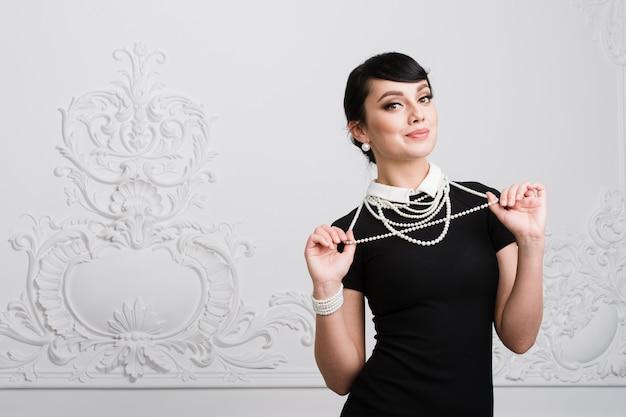 Mooie retro vrouw met parelshalsband bij luxebinnenland