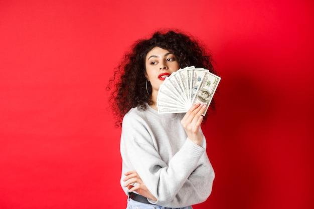 Mooie rijke vrouw die sensueel opzij kijkt, naar zichzelf zwaait met een ventilator van dollarbiljetten, verleidelijk staand op rode achtergrond
