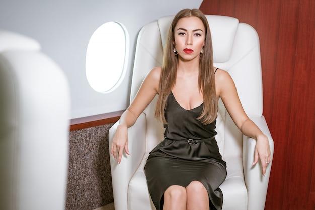 Mooie rijke vrouw in een privé eerste klas vliegtuig