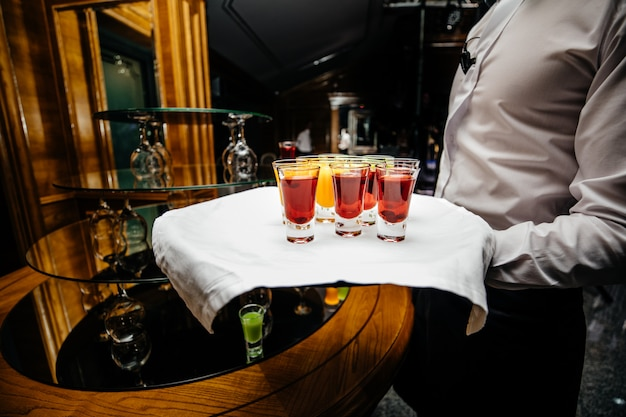 Mooie rijlijn van verschillende gekleurde alcoholcocktails op een partij verfraaide cateringboeketlijst op openluchtevenement, beeld met mooie bokeh