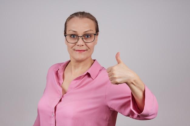 Mooie rijpe bedrijfsvrouw met glad-achterhaar dat duim toont. ik ben tevreden met het succesvolle werk. foto op een grijze achtergrond.