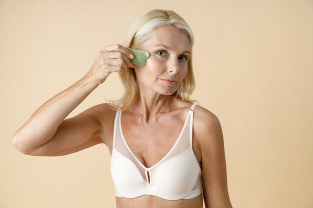 Mooie rijpe blonde vrouw in witte beha kijkend naar camera met jade gua sha massage tool voor