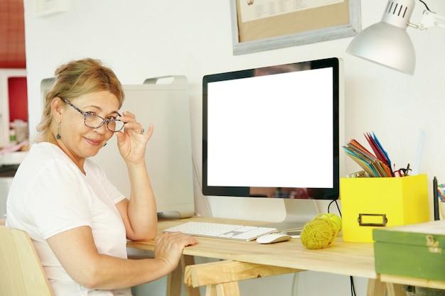 Mooie rijpe blonde vrouwelijke gepensioneerde die in bril achter computer zit