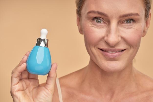 Mooie rijpe gelukkige vrouw die de fles anti-aging serum vasthoudt en glimlacht naar de camera