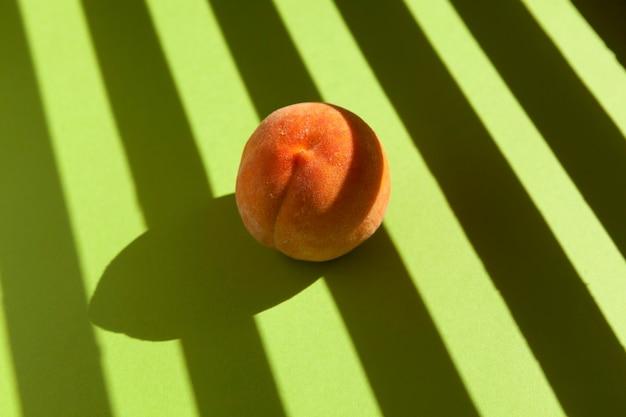 Mooie rijpe perzik op lichtgroen met gestreepte schaduwen van zonlicht