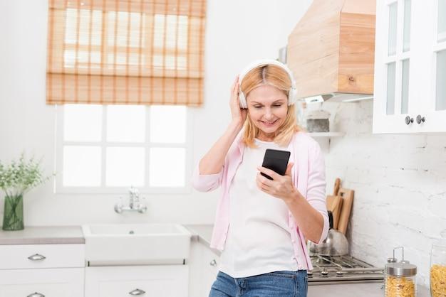 Mooie rijpe vrouw die aan muziek in de keuken luistert