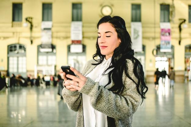 Mooie rijpe vrouw die de programma's van haar trein controleert op haar mobiele telefoon.