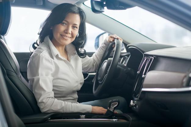 Mooie rijpe vrouw die nieuwe auto's controleert bij het dealership