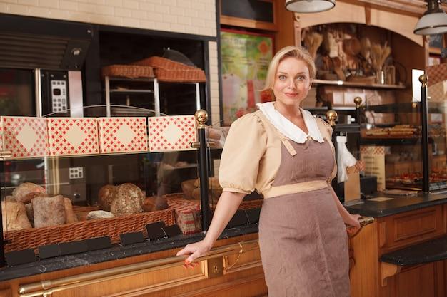 Mooie, rijpe vrouw die trots poseert in haar kleine bakkerijwinkel