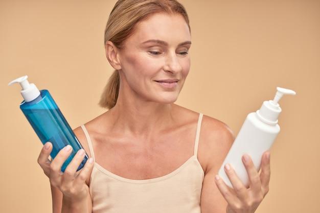 Mooie rijpe vrouw die tussen twee huidverzorgingsproducten kiest terwijl ze geïsoleerd over beige staat