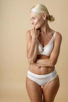 Mooie rijpe vrouw in ondergoed met een perfect lichaam dat opzij glimlacht en haar gezicht aanraakt geïsoleerd
