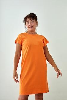 Mooie rijpe vrouw in oranje jurk witte achtergrond