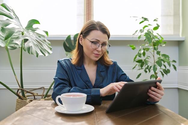 Mooie rijpe vrouw in pyjama lezen nieuws, sociale netwerken, mail in digitale tablet. ochtendportret van een vrouw van middelbare leeftijd thuis aan tafel met een kopje thee, ontbijt.