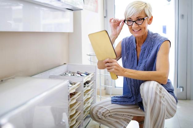 Mooie rijpe vrouw kiest nieuwe bril bij optiekwinkel