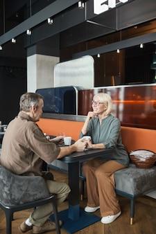 Mooie rijpe vrouw met blond haar aan tafel zitten en luisteren naar vriendje tijdens date in restaurant