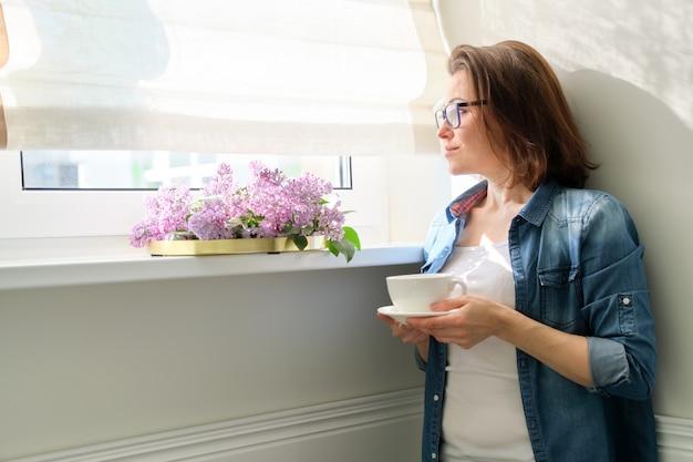 Mooie rijpe vrouw thuis met bloemen, glimlachende vrouw die zich dichtbij venster met kop thee bevindt