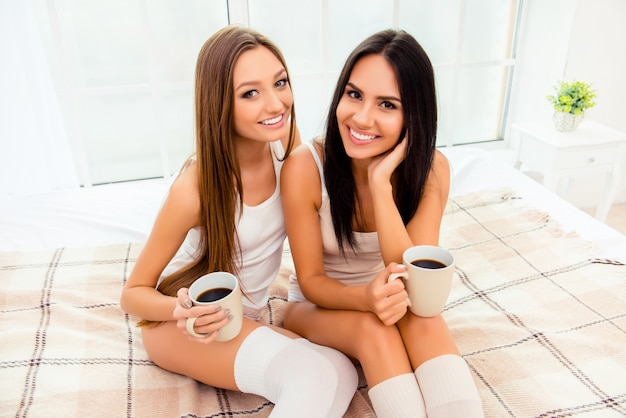 Mooie roddelmeisjes die koffie drinken en op het bed zitten