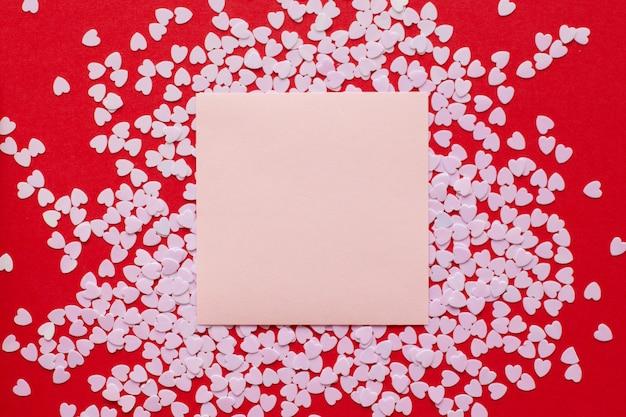 Mooie rode achtergrond met kleine harten en een vierkante ruimte in het midden om tekst toe te voegen