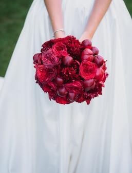 Mooie rode bruiloft boeket gemaakt van pioenrozen in de handen van de bruid