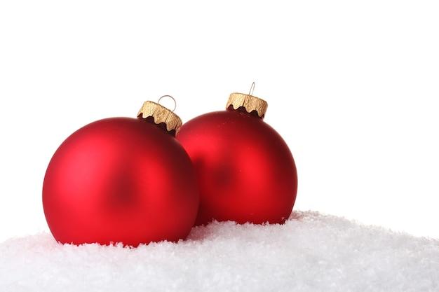 Mooie rode kerstbal in sneeuw geïsoleerd op wit