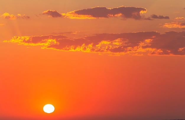 Mooie rode zonsondergang en felle zon aan de horizon