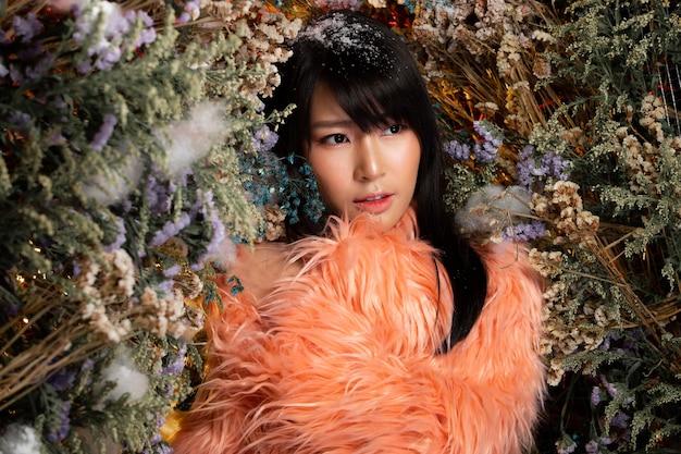 Mooie romantische jonge aziatische vrouw in oude roos bont doek in bush verscheidenheid van bloemen poseren op achtergrond verse en gedroogde flora. inspiratie van herfst winter sneeuw parfum, cosmetica concept.